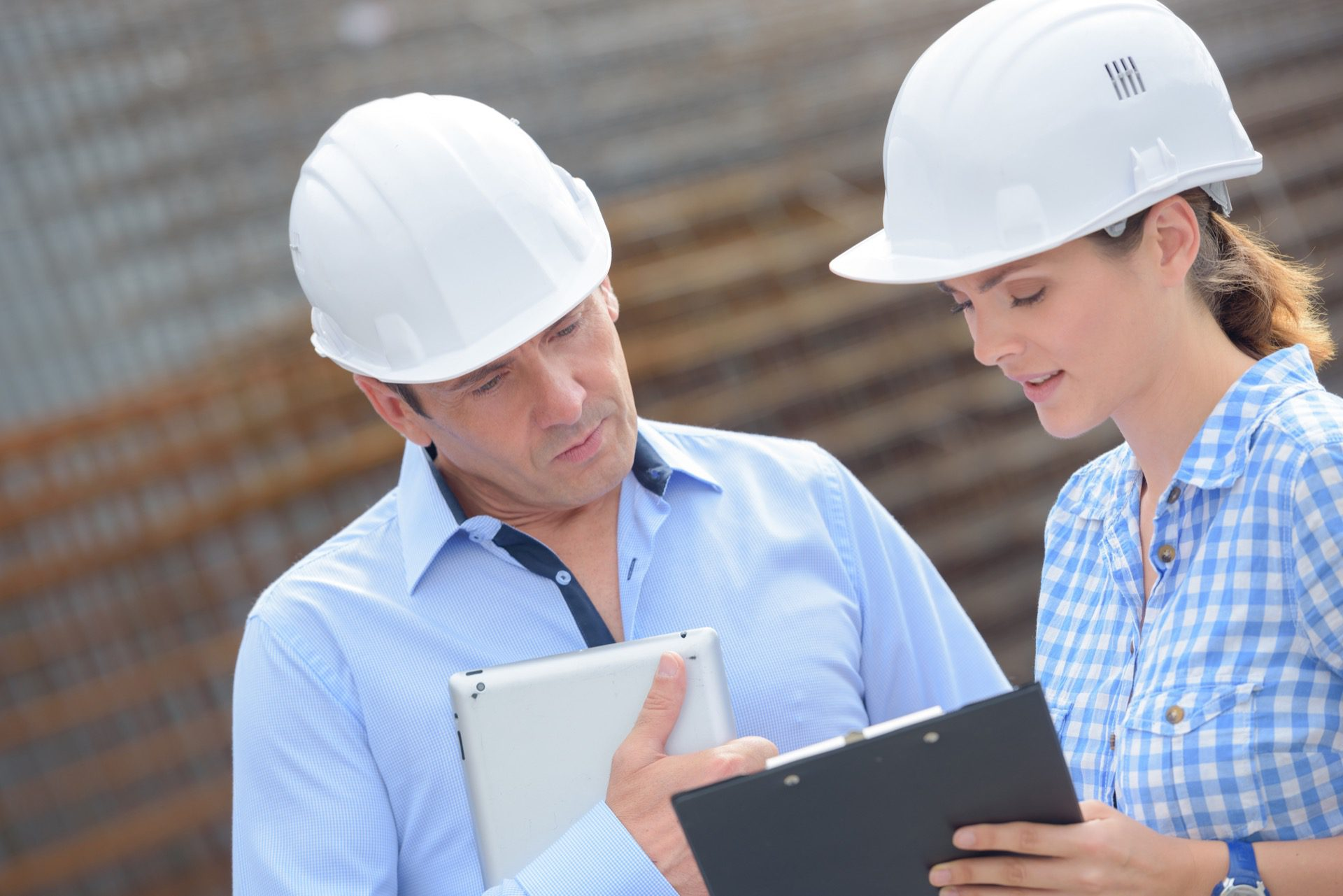 Woman and man in hardhats reviewing commercial real estate appraisal